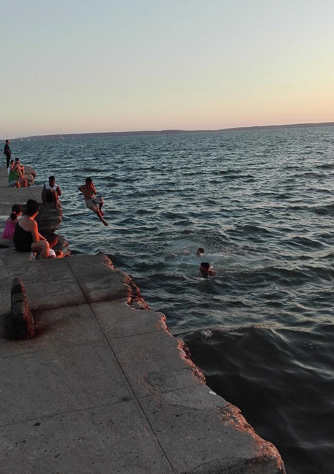 Los niños saltando desde el espigón al agua