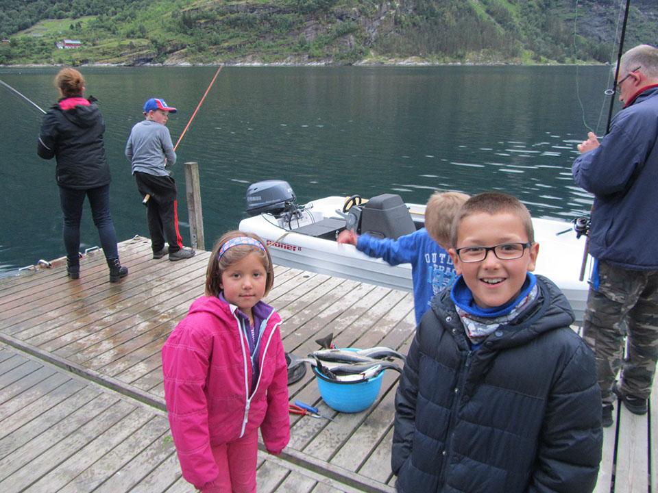 Familia pescando un montón de peces en el fiordo Geiranger en Noruega.